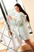 Beautiful woman hanging freshly washed clothes on the rack — Stock Photo