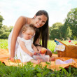Stock Photo: Young happy mother with daughter in the park picnicking