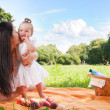 Young happy mother with daughter in park on picnic — Stock Photo