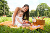 Young happy mother with daughter in the park picnicking — Stock Photo