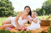 Genç mutlu anne ile kızı park piknik içinde — Stok fotoğraf