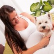 Happy pregnant woman with west highland white terrier relaxing o — Stock Photo #40555207