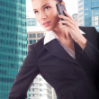 Smiling young business woman talking on the phone in the big cit — Stock Photo #40555243