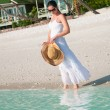 Beautiful woman walking along seaside on tropical beach — Stock Photo #40555307