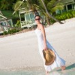 Beautiful woman walking along seaside on tropical beach — Stock Photo