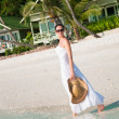 Beautiful woman walking along seaside on tropical beach — Stock Photo #41508927