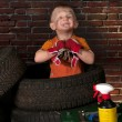Cute and funny little mechanic with a tire — Stock Photo #48561839