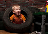 Cute and funny little mechanic with a tire — Stock Photo