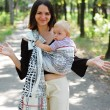 Young mother carrying her child in a baby carrier — Stock Photo