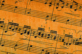 Music notes on old paper sheet background — Stock Photo