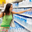 A woman buys a bottle of water in the store — Stock Photo #18035663