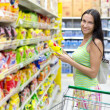 Woman buys potato chips in the store — Stock Photo