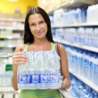 A woman buys a bottle of water in the store — Stock Photo #18036469