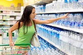 A woman buys a bottle of water in the store — Stock Photo