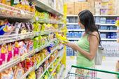 Vrouw koopt potato chips in de winkel — Stockfoto