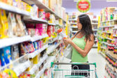 Woman checking food labelling — Stockfoto