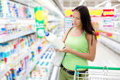The woman buyer in shop chooses milk — Stock Photo