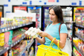 A woman buys tinned meat — Stock Photo