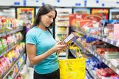 Mujer comprobando el etiquetado de los alimentos — Foto de Stock