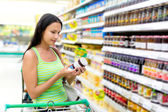 Woman buys a jam in the store — Stock Photo