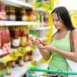Woman checking food labelling - Stock Photo