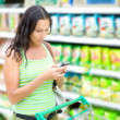 A woman reads SMS in supermarkets — Stock Photo