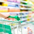 Cropped image of female shopper with cart at supermarket - Stock Photo