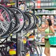 Stock Photo: Womlooking bikes in supermarket