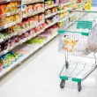 Stock Photo: Shopping trolley in aisle of supermarket