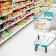 Shopping trolley in aisle of supermarket — Stock Photo #24389983