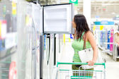 A woman buys a refrigerator in the store — Stock Photo