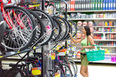 Woman looking bikes in the supermarket — Stock Photo