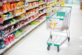 Shopping trolley in aisle of supermarket — 图库照片