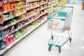 Winkelwagentje in gangpad van de supermarkt — Stockfoto