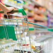 Stock Photo: Female customer shopping at supermarket with trolley