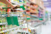 Vrouwelijke klant winkelen bij de supermarkt met trolley koffer — Stockfoto