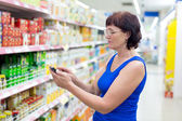 Woman reads SMS in supermarkets — Stock Photo