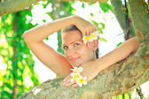 Woman with tropic flowers — Stock Photo