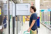 Man choosing fridge — Stock Photo