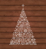 Christmas pine made of snowflakes on wooden background — Stock Vector