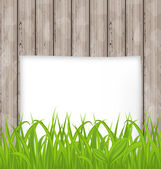 Green grass and paper sheet on wooden texture — Vetor de Stock