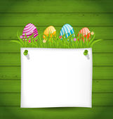Easter colorful eggs in green grass with empty paper card for y — Stock Vector