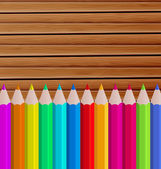Palette pencils on wooden background — Stock Vector