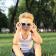 Little boy sitting in the park — Stock Photo