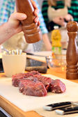 Man is salting a meat — Stock Photo