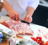 Chef cook cuts a meat — Stock Photo