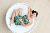 Young woman lies in the circle chaise-longue — Stock Photo