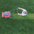 Little boy cuts a grass using lawn-mower — Stock Photo