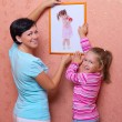 Woman and her daughter hanging up photo (of same girl) — Stock Photo