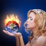Frozen girl holding burning earth globe — Stock Photo #13169856